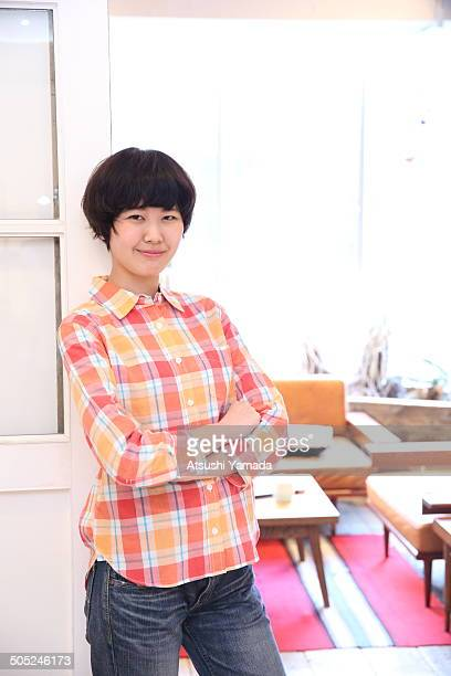 Young Japanese woman standing in cafe