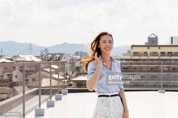 young japanese woman standing on a rooftop in an urban setting, looking at camera. - 30代の女性一人 ストックフォトと画像