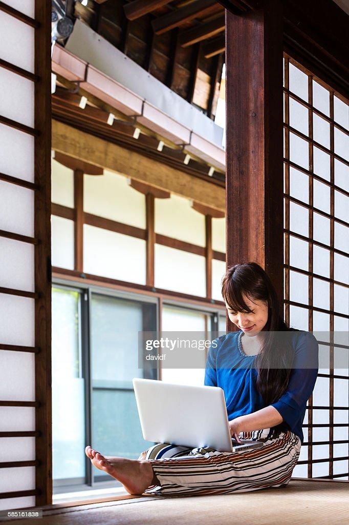 伝統的な畳の部屋でノートパソコンを使った日本の若い女性 : ストックフォト