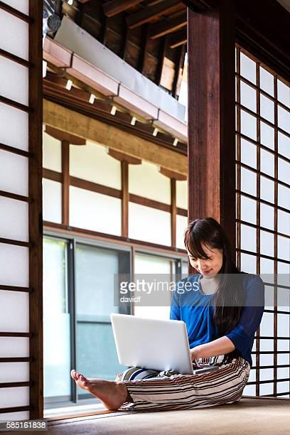 伝統的な畳の部屋でノートパソコンを使った日本の若い女性 - 和室 ストックフォトと画像