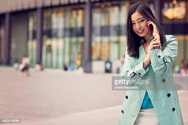 Jovem mulher a utilizar telemóvel Japonês