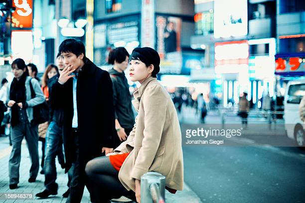 Young Japanese woman waiting for her friends, sitting on a railing along a busy, crowded sidewalk in Shibuya in the evening.