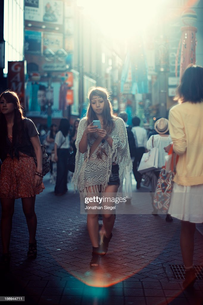 Young Japanese woman walking forward and away from the sunset while using her mobile phone in Shibuya, Tokyo.