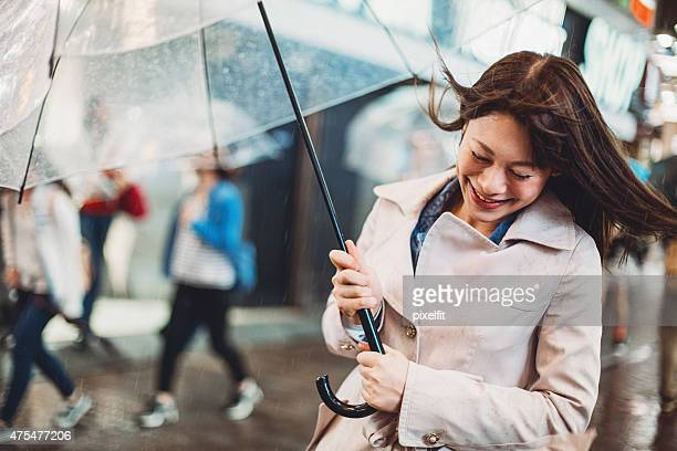 Young Japanese woman walking happy in the rain