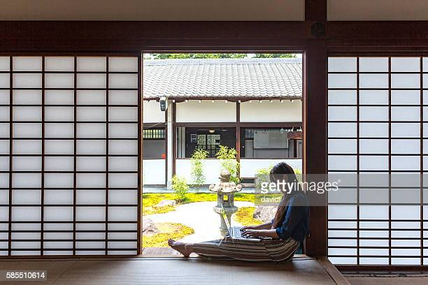young japanese woman with computer in traditional temple tatami room - shrine stock pictures, royalty-free photos & images