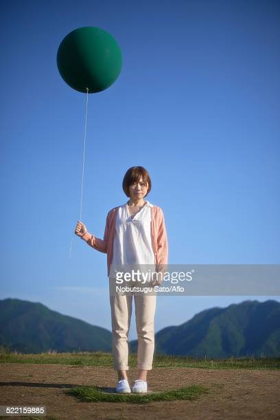 young japanese woman with green balloon in the countryside - チノパンツ ストックフォトと画像
