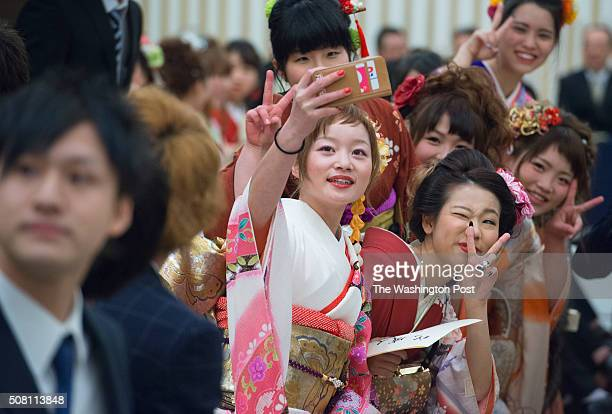 Young japanese women and men take 'selfies' during the Seijin no Hi ceremony in Kanazawa Japan on January 10 2016 Japanese men and women who have...