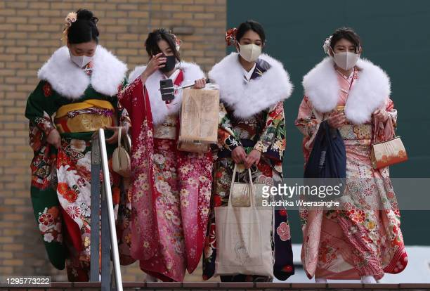Young Japanese women dressed in traditional kimonos and wearing face masks attend an out-door Coming-of-Age ceremony at Koshien national high school...