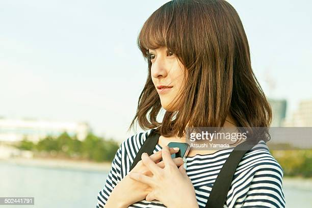 Young Japanese women holding smartphone on beach