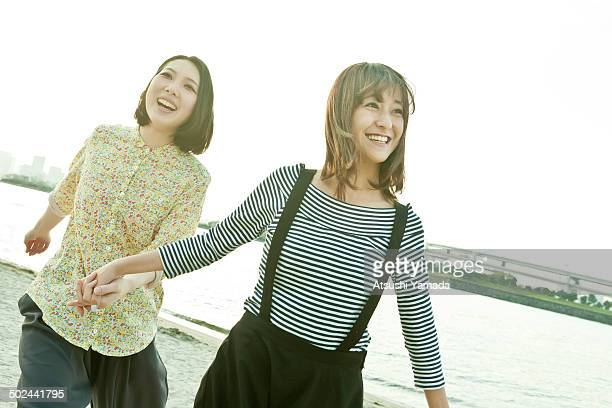 young japanese women running on beach,smiling - suspenders stock pictures, royalty-free photos & images