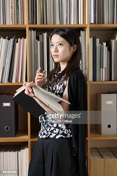 Young japnese girl in front of the bookshelf