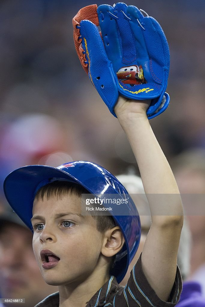 TORONTO - AUGUST 26 - A young Jays fan with a pint sized glove, stands at the ready for a ball. Toronto Blue Jays Vs Boston Red Sox during MLB action at Rogers Centre on August 26, 2014.