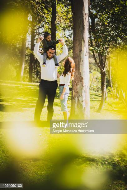 a young jewish family in a park with the father carrying the young boy in his shoulders - judaism stock pictures, royalty-free photos & images