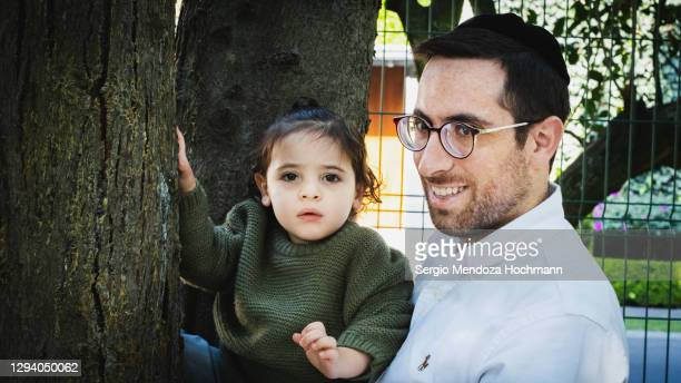 a young jewish father with his young boy - スカルキャップ ストックフォトと画像