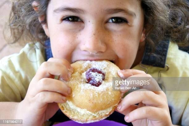 young jewish girl eating doughnut on the jewish holiday of hanukkah - rafael ben ari foto e immagini stock