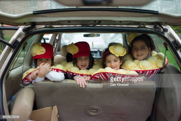 Young Jewish girls in fancy dress sit in the back of a car during the annual Jewish holiday of Purim on March 12 2017 in London England Purim is...