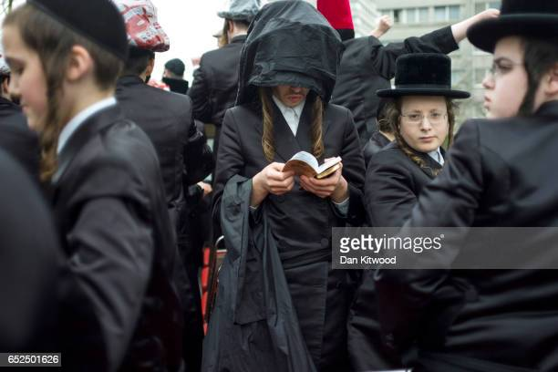 Young Jewish man reads a holy text on the top of an open top bus as it makes its way around the streets during the annual Jewish holiday of Purim on...