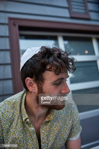 a young jewish man sitting at a table outside wearing a yamika, looking off camera. - judaism stock pictures, royalty-free photos & images