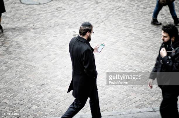 New York City - December 6, 2016: A young Jewish man wearing a traditional yarmulke consults his smartphone as he walks on Wall Street.