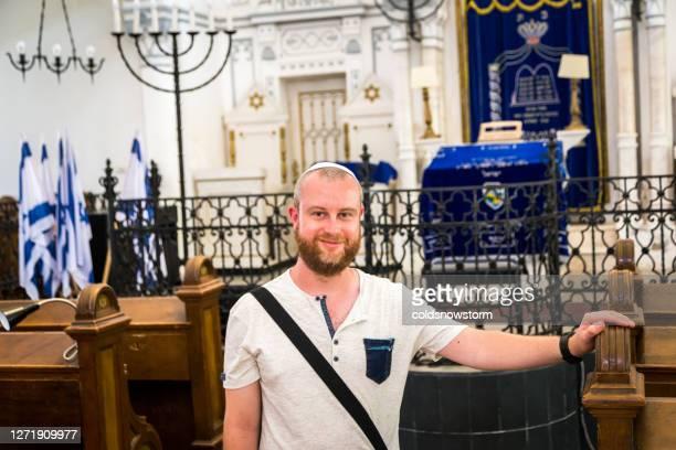 シナゴーグの中に頭蓋骨の帽子をかぶった若いユダヤ人男性 - ラビ ストックフォトと画像