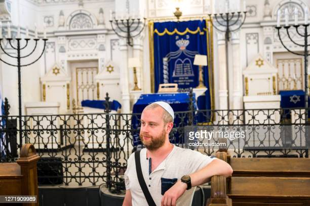 young jewish man wearing skull cap inside synagogue - rabbi stock pictures, royalty-free photos & images