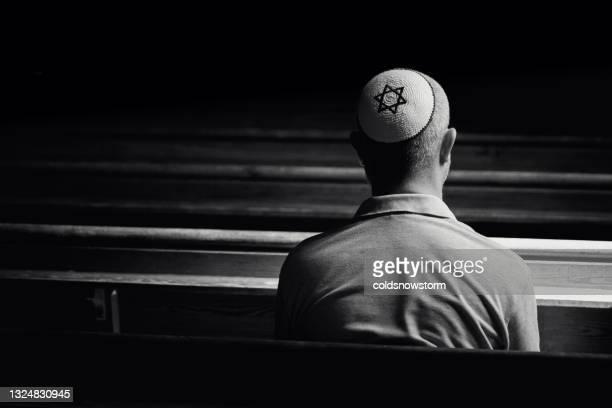 シナゴーグの中で祈る頭蓋骨の帽子をかぶった若いユダヤ人男性 - ラビ ストックフォトと画像