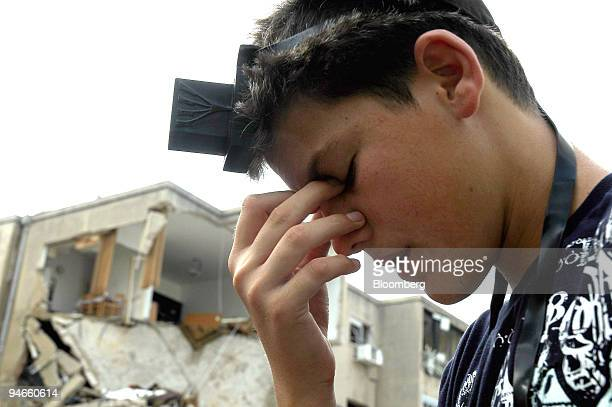 A young Jewish man wearing tefillin prays next to a building directly hit by a Hezbollah rocket from Lebanon in Haifa Israel Monday July 17 2006