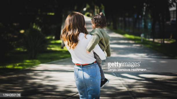a young jewish mother with her young boy, walking away from the camera - judaism stock pictures, royalty-free photos & images
