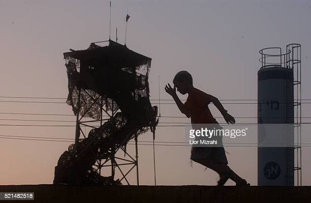 A young Jewish settler is silhouetted as he runs past an army watchtower in the Jewish settlement of Morag in the Gaza Strip Wednesday July 13 2005...