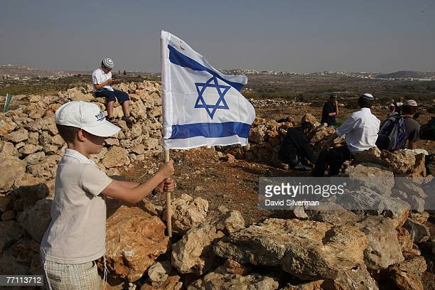 Young Jewish settler plants his flag on a stone wall built by settlers as they establish an unauthorised outpost September 30, 2007 on a hilltop...