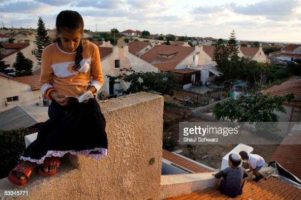 A young Jewish settler sits on a roof during a mass prayer aimed against the Israeli disengagement plan due to start next week August 9 2005 in Neve...