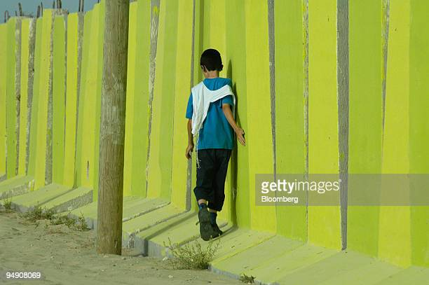 Young Jewish settler wears a prayer shawl next to a concrete defense wall in Shirat Hayam settlement, Friday, July 15, 2005. Jewish settlements are...