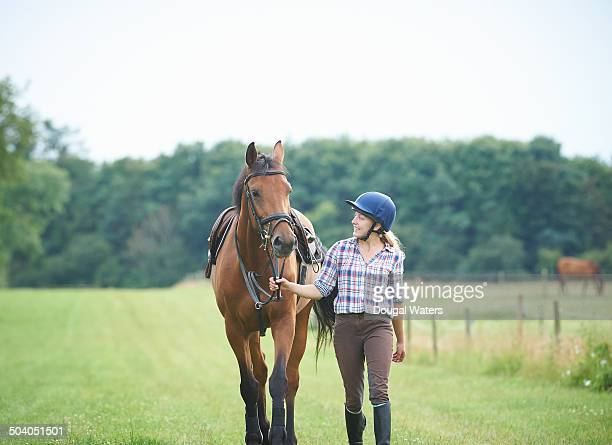 young jockey and horse walking in field. - 家畜 ストックフォトと画像