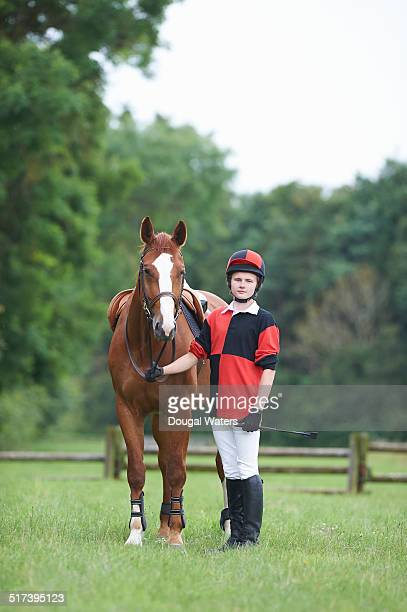 Young jockey standing with horse.