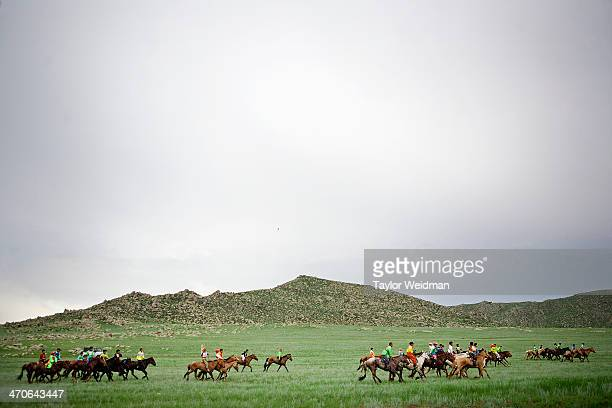 Young jockeys ride their horses out to the starting line for a race during a Naadam festival Mongolian pastoral herders make up one of the world's...