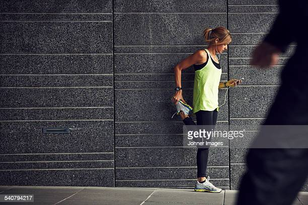 Young jogger stretching with cell phone against grey wall