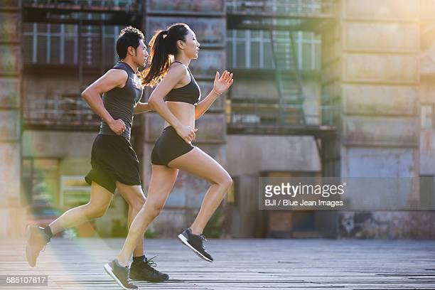 young joggers running outdoors - asian female bodybuilder stock photos and pictures