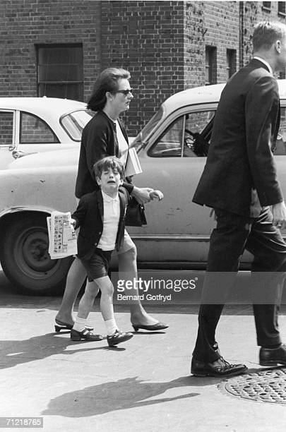 Young John F Kennedy Jr wearing short pants turns towards the camera and cries while holding the hand of a unidentified woman circa 1965
