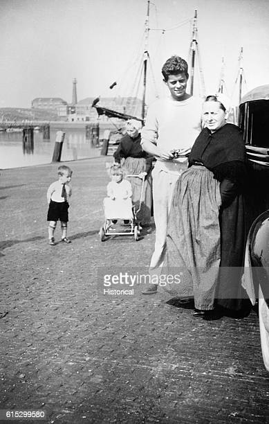 A young John F Kennedy talking to an elderly woman on the waterfront at Scheveningen The Hague Netherlands during his tour of Europe 25th August 1937