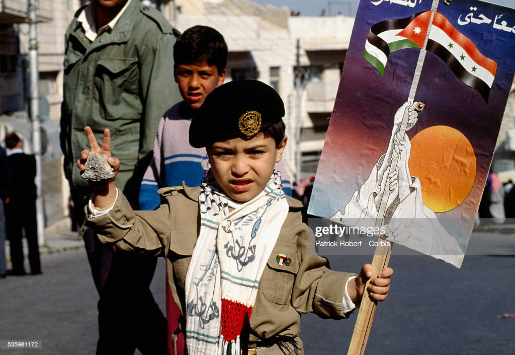 A young Jordanian boy gives the peace sign while holding a rock and sign depicting an Iraqi-Palestinian unity image following Friday prayers in Amman, Jordan.