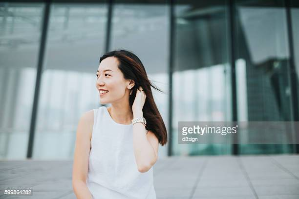 Young joyful woman enjoying the breeze and looking away in the city