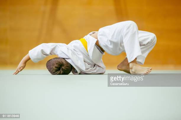 young judo student limbering up before judo training - judo stock photos and pictures