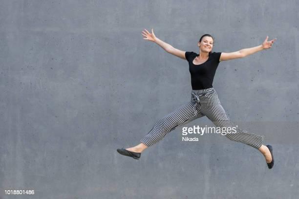 Springenden Mädchen vor einer grauen Wand