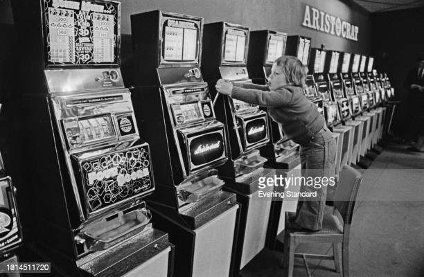 Young Justin Green tries his luck at a row of Aristocrat slot machines, UK, 30th January 1974.