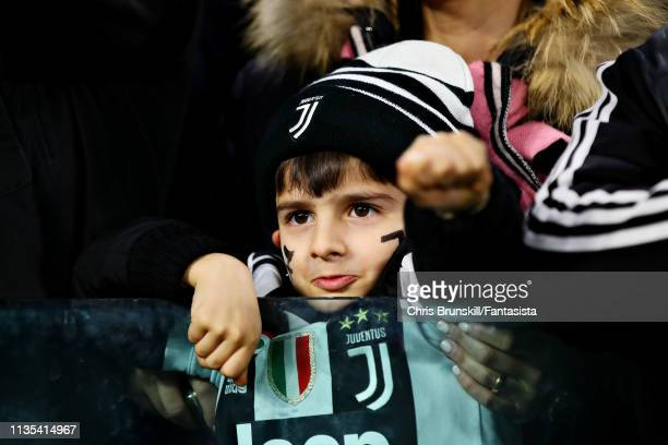 A young Juventus fan supports his team during the UEFA Champions League Round of 16 Second Leg match between Juventus and Club de Atletico Madrid at...