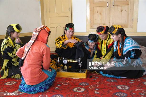 Young Kalash girls look at a woman who shows how to sew in Chitral in northern Khyber Pakhtunkhwa, Pakistan on January 02, 2020. Kalash people who...