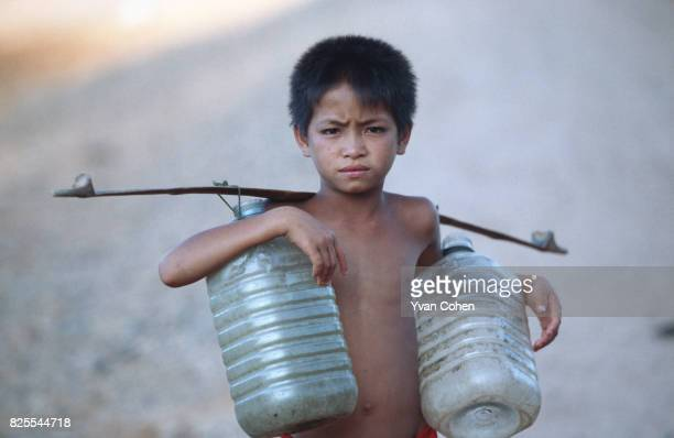 A young Karen refugee boy carries empty containers to a water supply point at Huay Galok refugee camp He is one of thousands of Karen refugees...