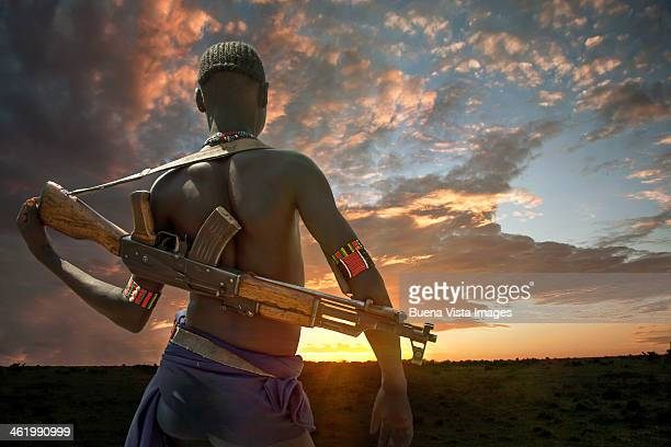 Young Karo Tribe man with semi-automatic rifle