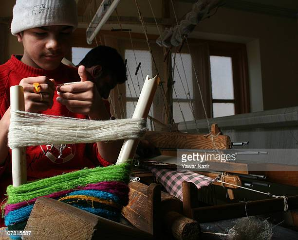 A young Kashmiri artisan collects pashmina threads on a twig used to weave Kani or Jamewar shawls at his workshop December 29 2010 on the outskirts...