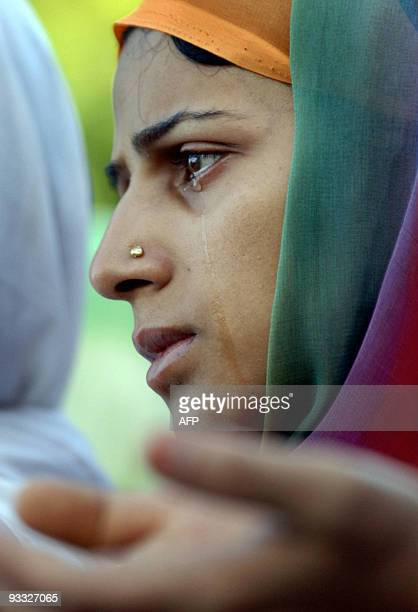 A young Kashmiri Muslim woman weeps as she offers prayers on the Friday following 'ShabeMeraj' at the famous Hazratbal Shrine in Srinagar 17 August...